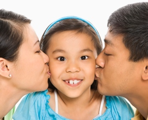 Parents kissing girl.